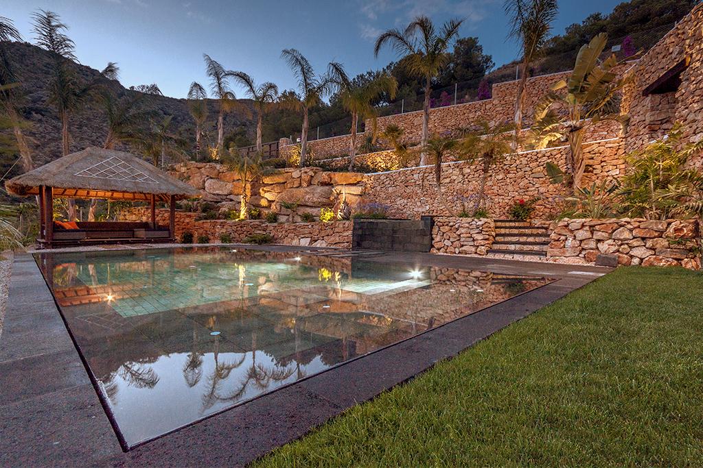 piscina iluminada Piscina desbordante perimetral con materiales de Indonesia.