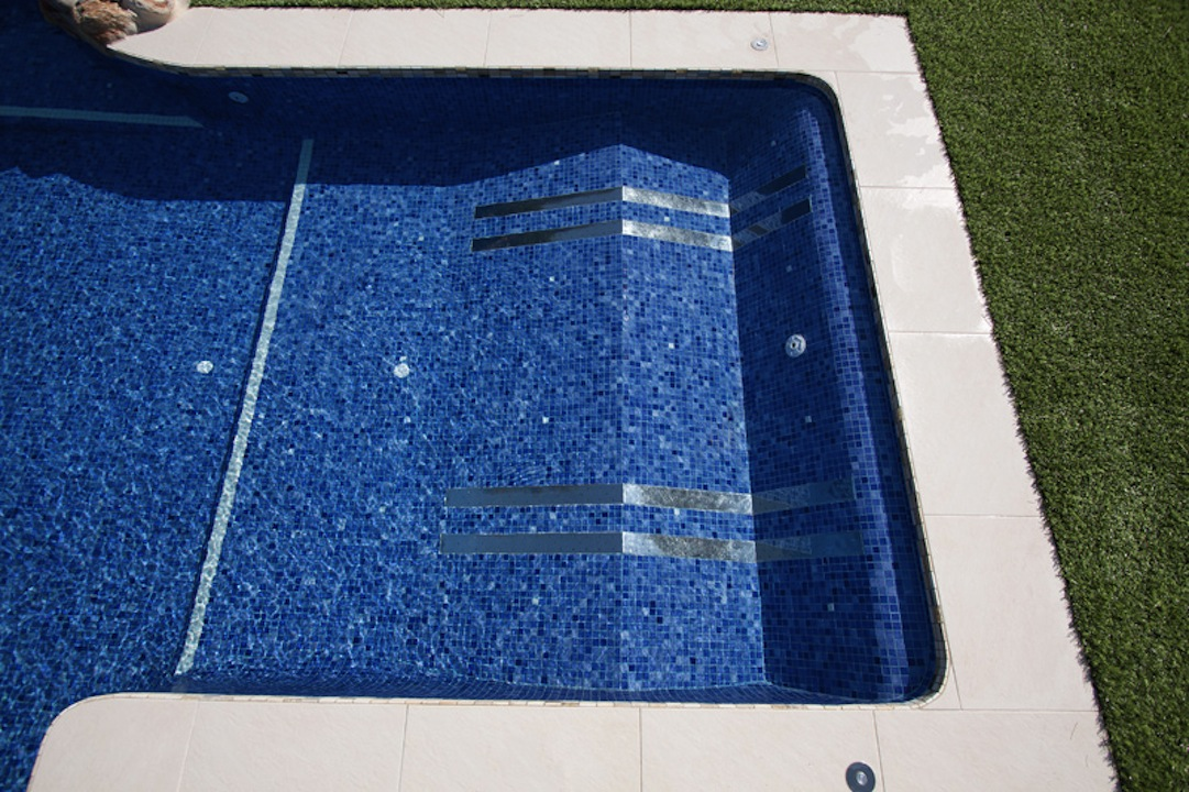 piscina con camas masaje Un spa en la piscina.