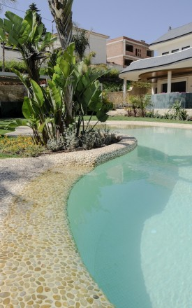 efecto desbordante piscinas1 275x440 Piscina con revestimiento de piedra canto rodado y gresite color crema.