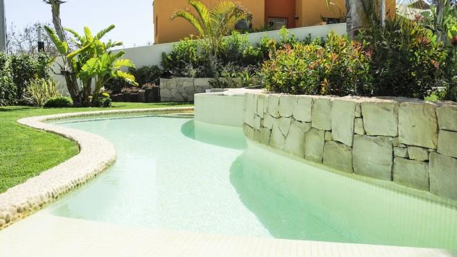 piedra en piscinas1 660x371 Piscina con revestimiento de piedra canto rodado y gresite color crema.