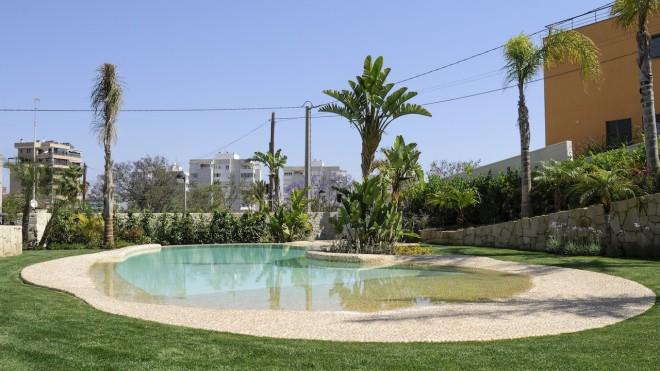 piscina color verde1 660x371 Piscina con revestimiento de piedra canto rodado y gresite color crema.