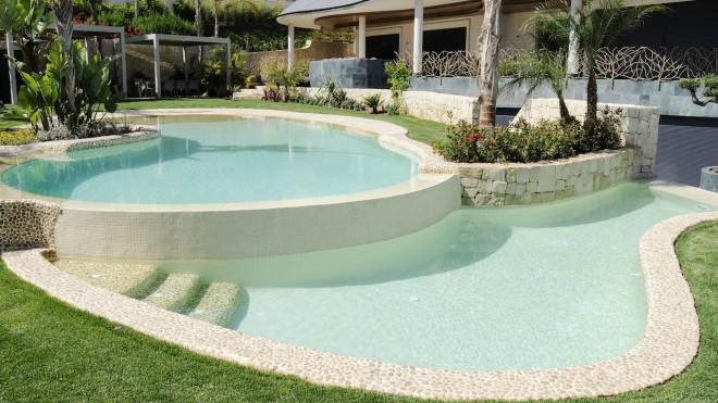 piscina infinity con cascadas 660x371 Piscina con revestimiento de piedra canto rodado y gresite color crema.