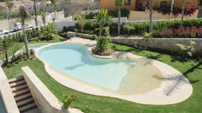 piscina natural 660x371 Piscina con revestimiento de piedra canto rodado y gresite color crema.